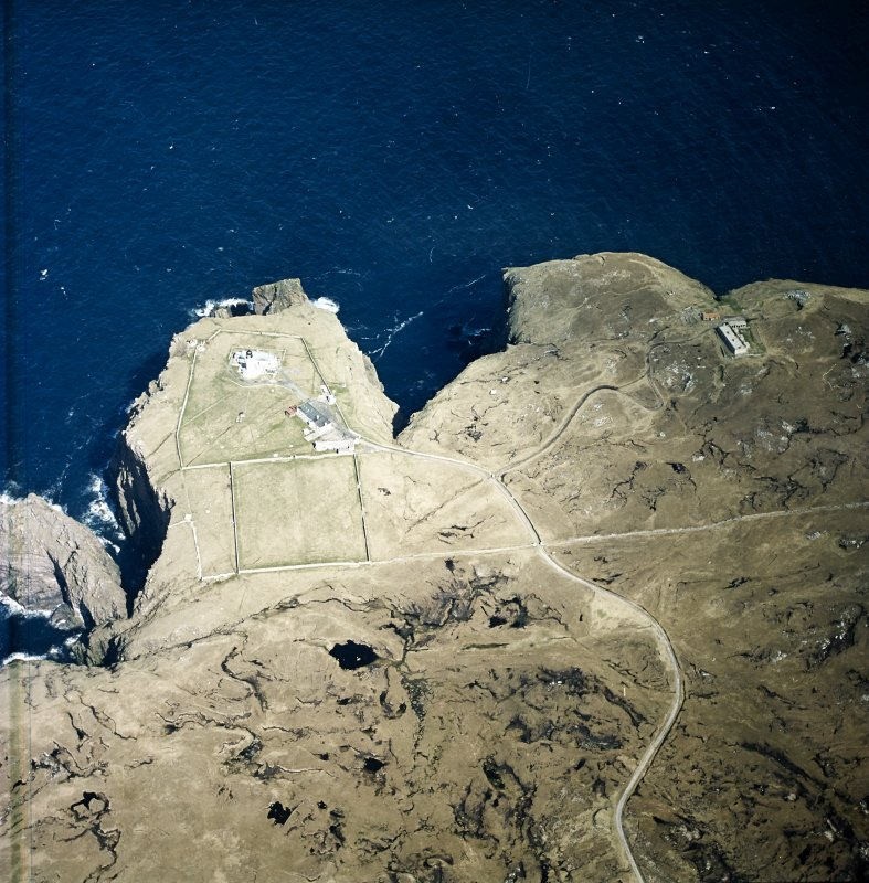 Oblique aerial view centred on the lighthouse, keepers' cottages, cottages and support buildings with the radar station adjacent, taken from the SW.