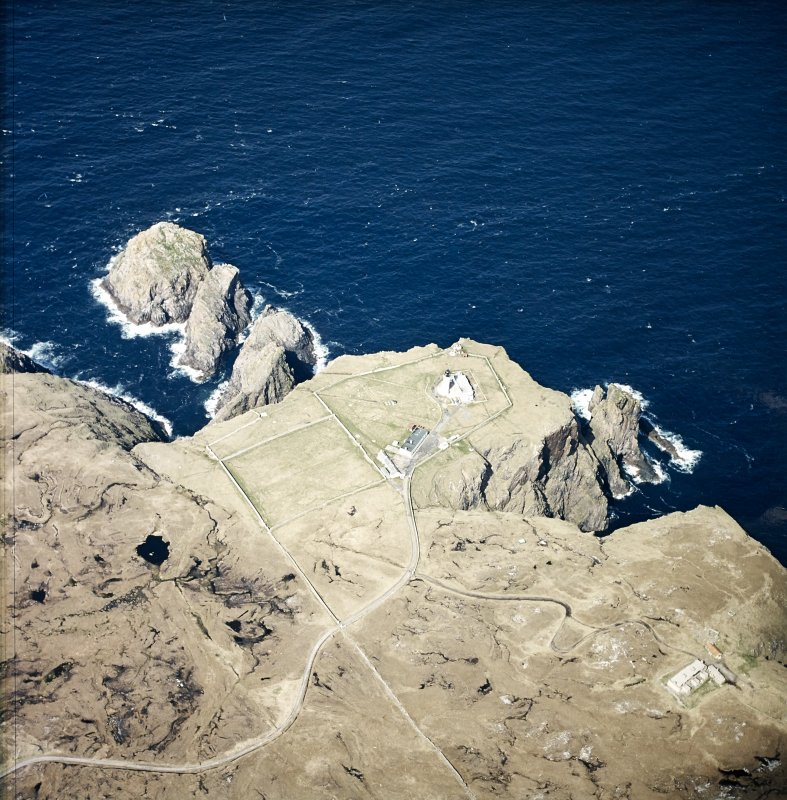 Oblique aerial view centred on the lighthouse, keepers' cottages, cottages and support buildings with the radar station adjacent, taken from the SSE.