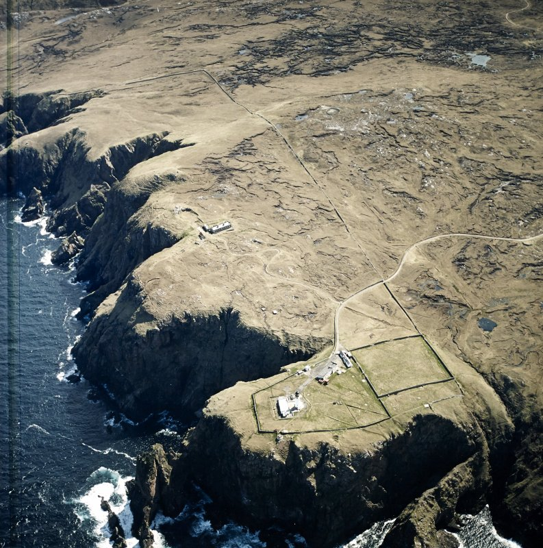 Oblique aerial view centred on the lighthouse, keepers' cottages, cottages and support buildings with the radar station adjacent, taken from the NNW.