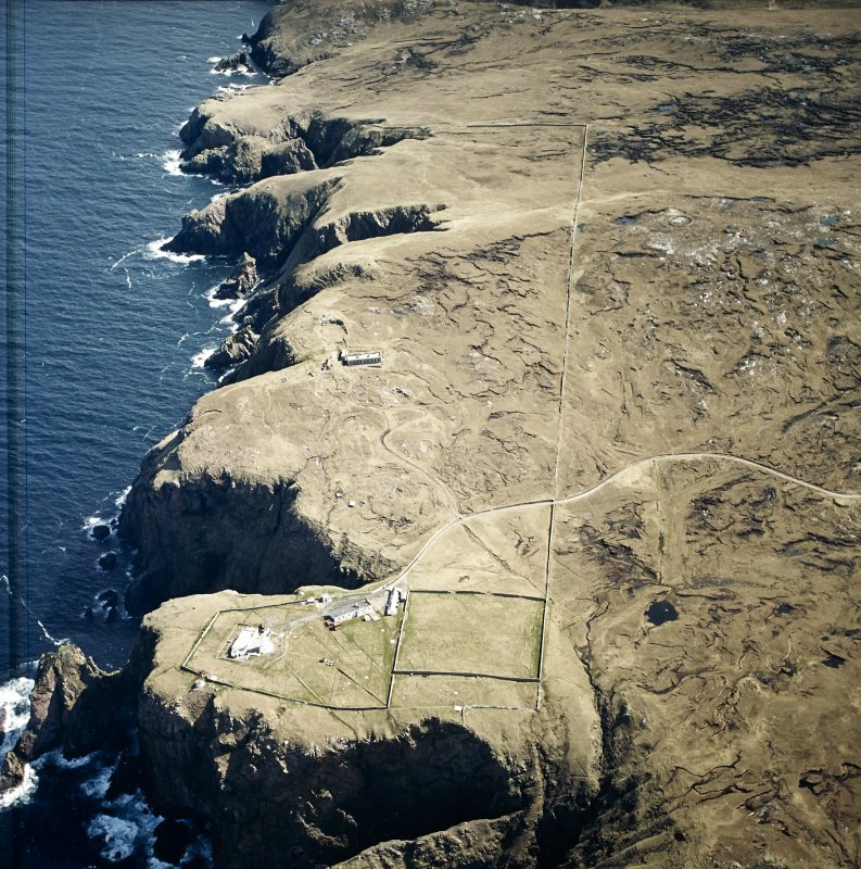 Oblique aerial view centred on the lighthouse, keepers' cottages, cottages and support buildings with the radar station adjacent, taken from the NW.