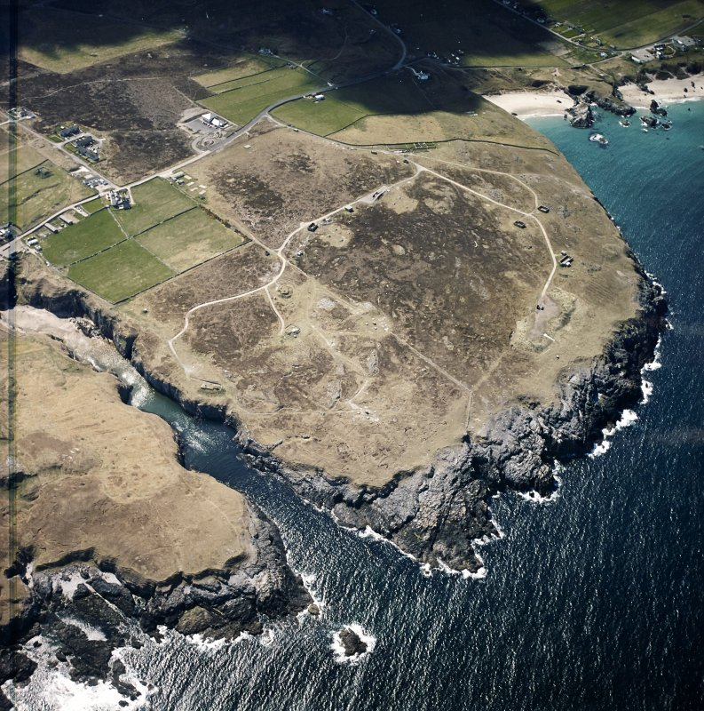Oblique aerial view centred on the remains of the radar station with caves and crofting township adjacent, taken from the ENE.