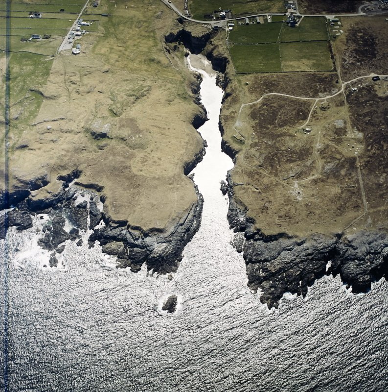 Oblique aerial view centred on the Smoo cave with the remains of the radar station and crofting townships adjacent, taken from the NE.