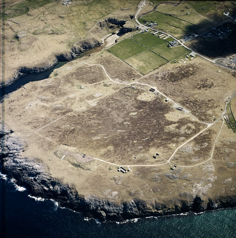 Oblique aerial view centred on the remains of the radar station with caves and crofting township adjacent, taken from the NW.
