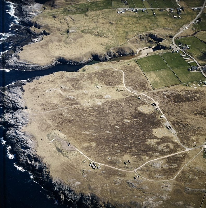 Oblique aerial view centred on the remains of the radar station with caves and crofting townships adjacent, taken from the NW.