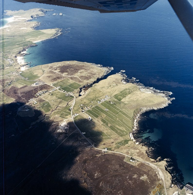 General oblique aerial view centred on the crofting townships, cave and the remains of the radar station, taken from the SSE.