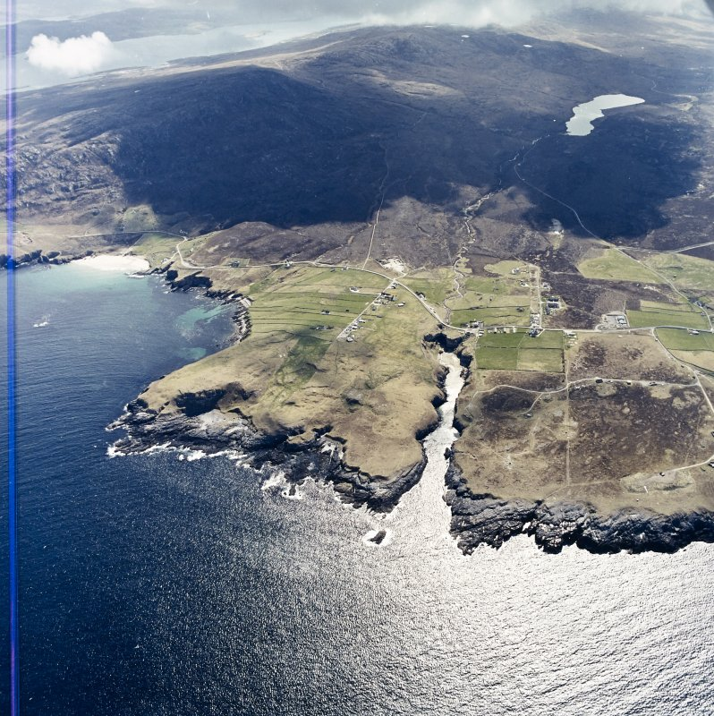 General oblique aerial view centred on the crofting townships, cave and the remains of the radar station, taken from the NNE.