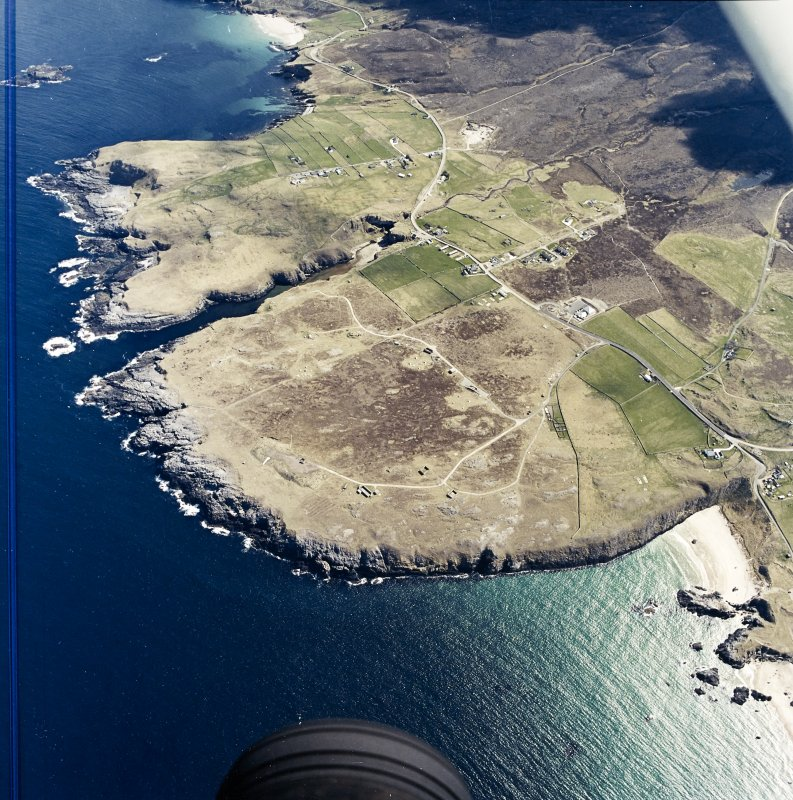 General oblique aerial view centred on the crofting townships, cave and the remains of the radar station, taken from the NW.