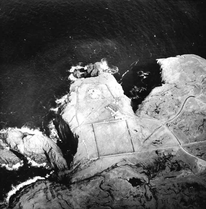 Oblique aerial view centred on the lighthouse, keepers' cottages, cottages and support buildings, taken from the SW.