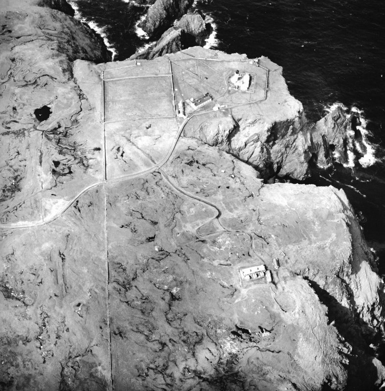 Oblique aerial view centred on the lighthouse, keepers' cottages, cottages and support buildings with the radar station adjacent, taken from the SE.