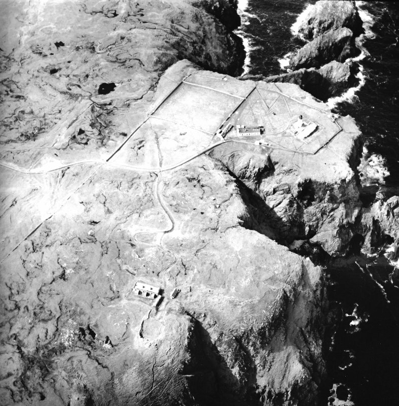 Oblique aerial view centred on the lighthouse, keepers' cottages, cottages and support buildings with the radar station adjacent, taken from the ESE.