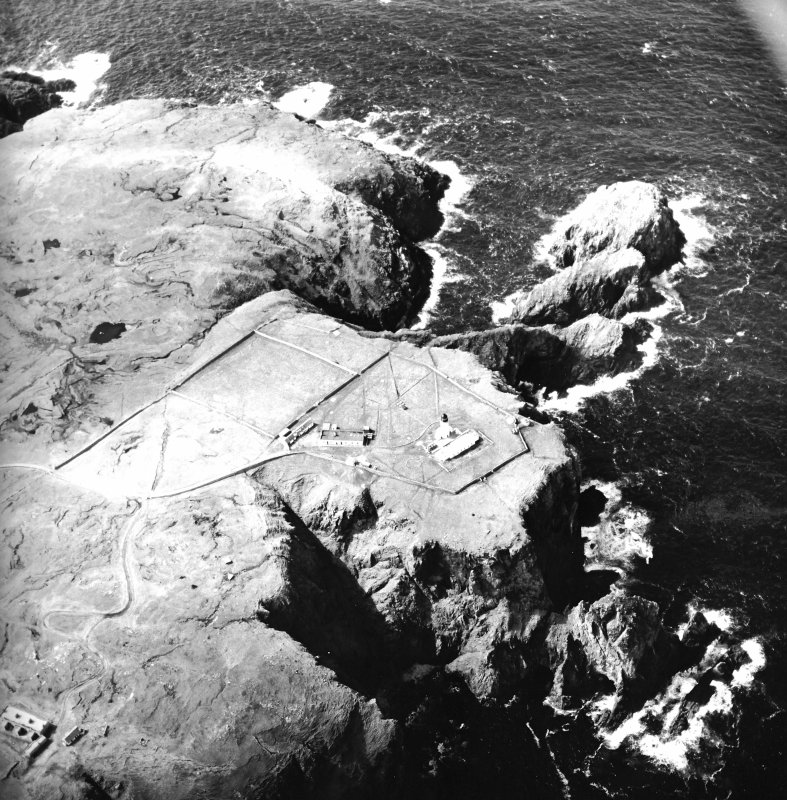 Oblique aerial view centred on the lighthouse, keepers' cottages, cottages and support buildings with the radar station adjacent, taken from the E.