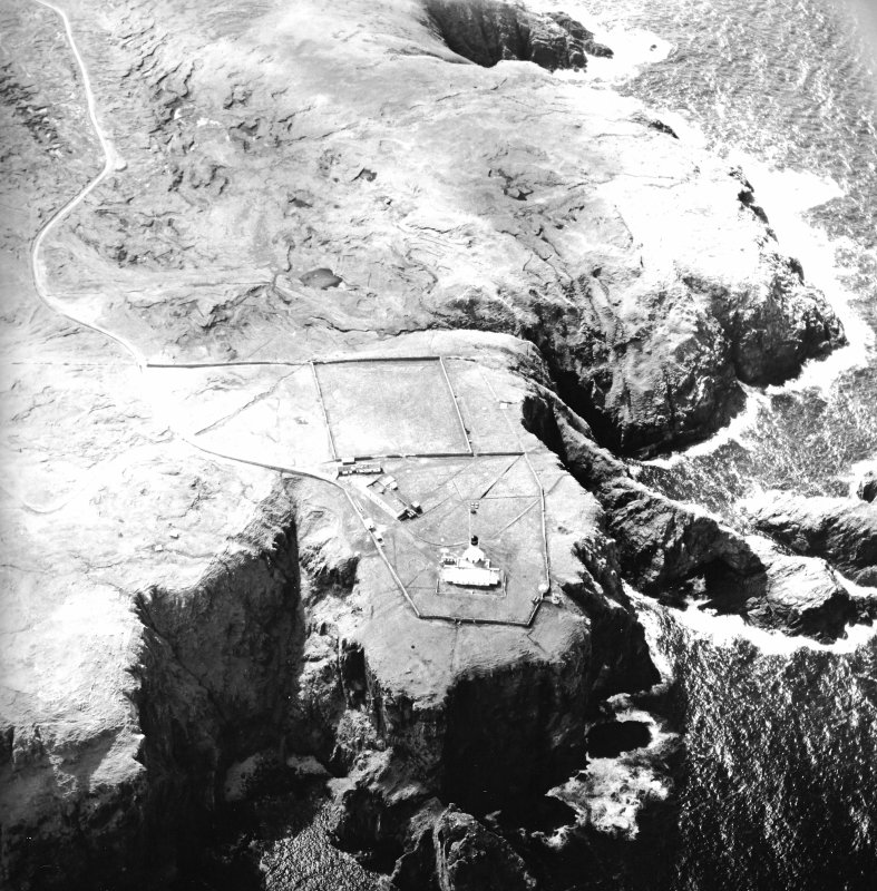 Oblique aerial view centred on the lighthouse, keepers' cottages, cottages and support buildings, taken from the NE.