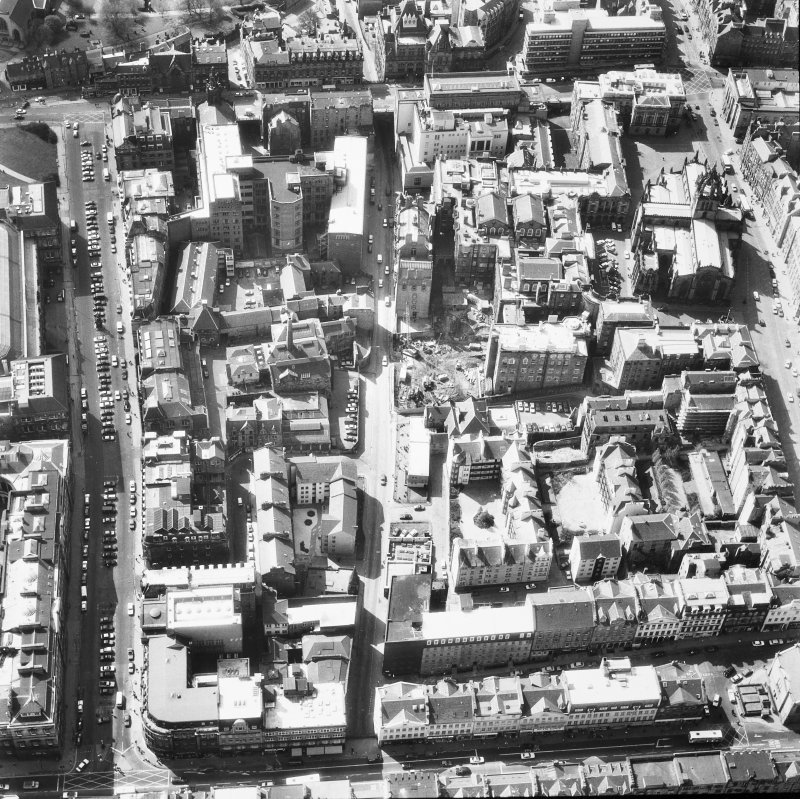 Oblique aerial view of Cowgate and surrounding area, including Chambers Street to left of photograph, George IV Bridge at top, High Street to right and South Bridge at bottom