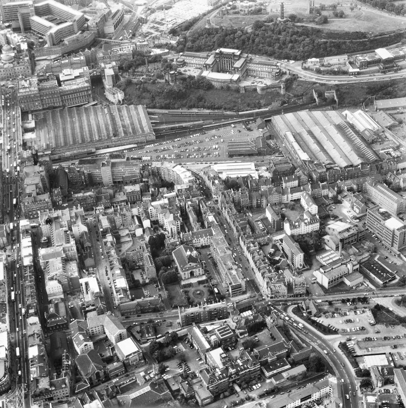 Aerial view showing Canongate and High Street running across centre of photograph, with North and South Bridges to left, Calton Hill at top, Moray House College to right and Cowgate at bottom