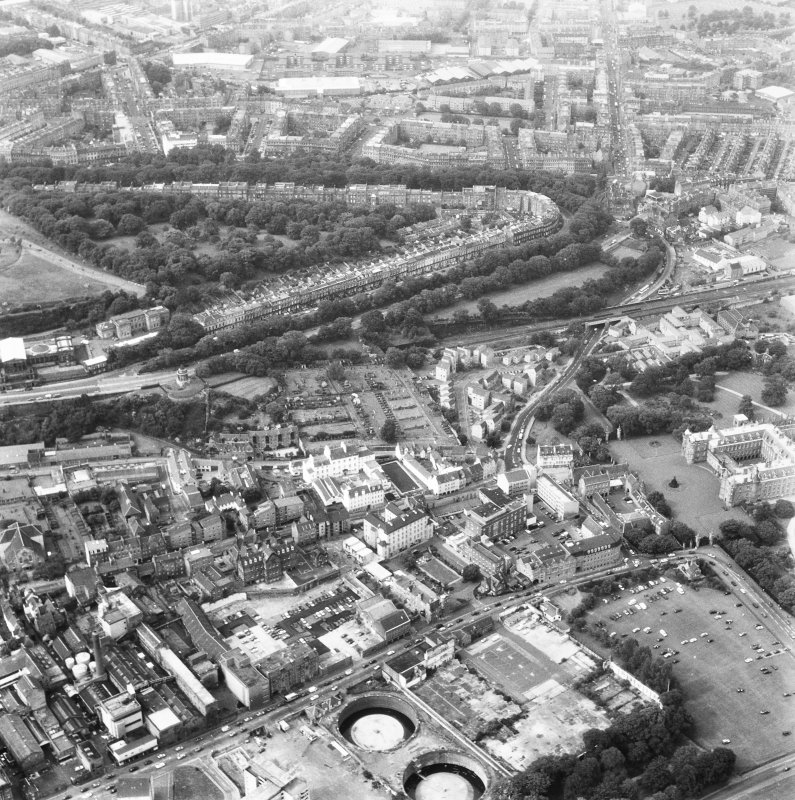 Aerial view of lower end of Canongate, also showing Regent Terrace towards top of photograph, Holyrood Palace at right, Holyrood Road, Meadow Flat Gas Holder Station at bottom, and Canongate heading to left