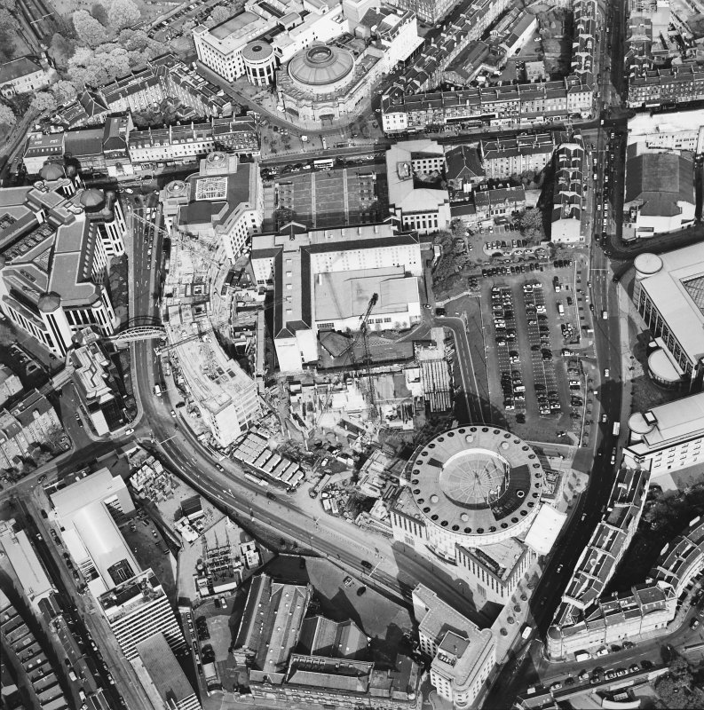Oblique aerial view of Edinburgh centred on the construction of Exchange Crescent, taken from the W.