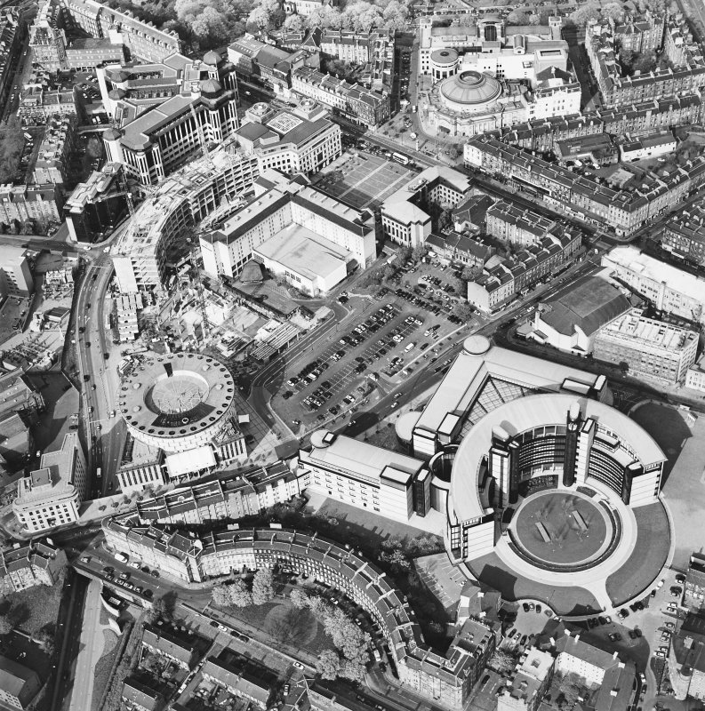 Oblique aerial view of Edinburgh centred on the Exchange area with the Scottish Widows building and construction of Exchange Crescent visible, taken from the SW.