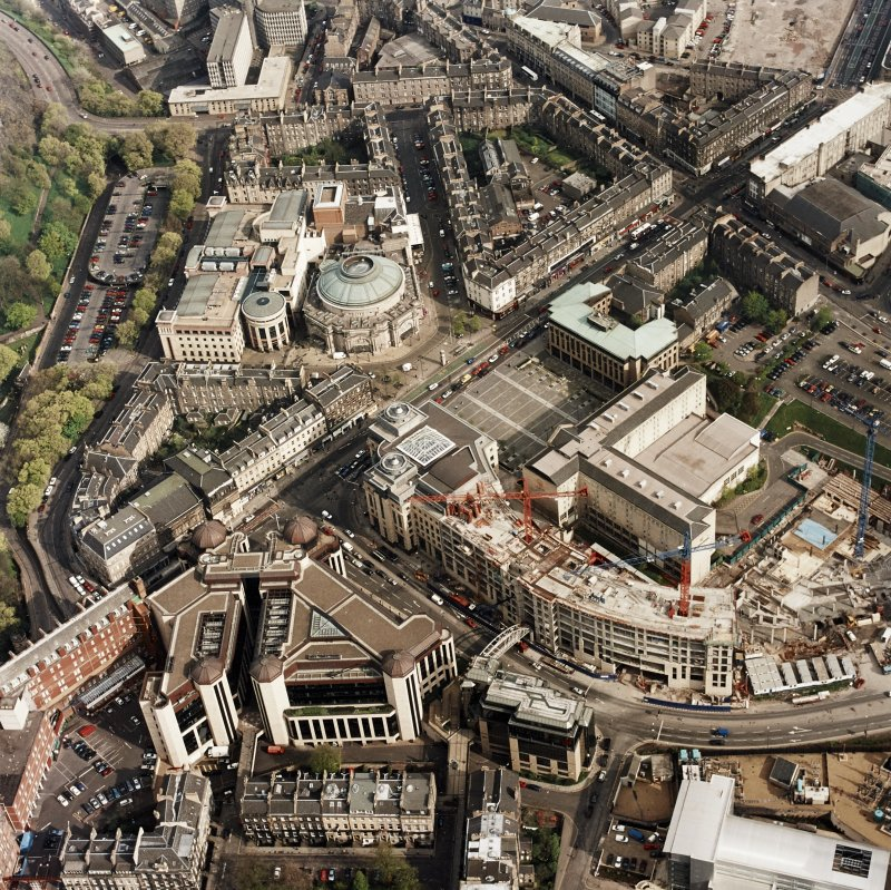 Oblique aerial view of Edinburgh centred on the construction of Exchange Crescent, taken from the NW.