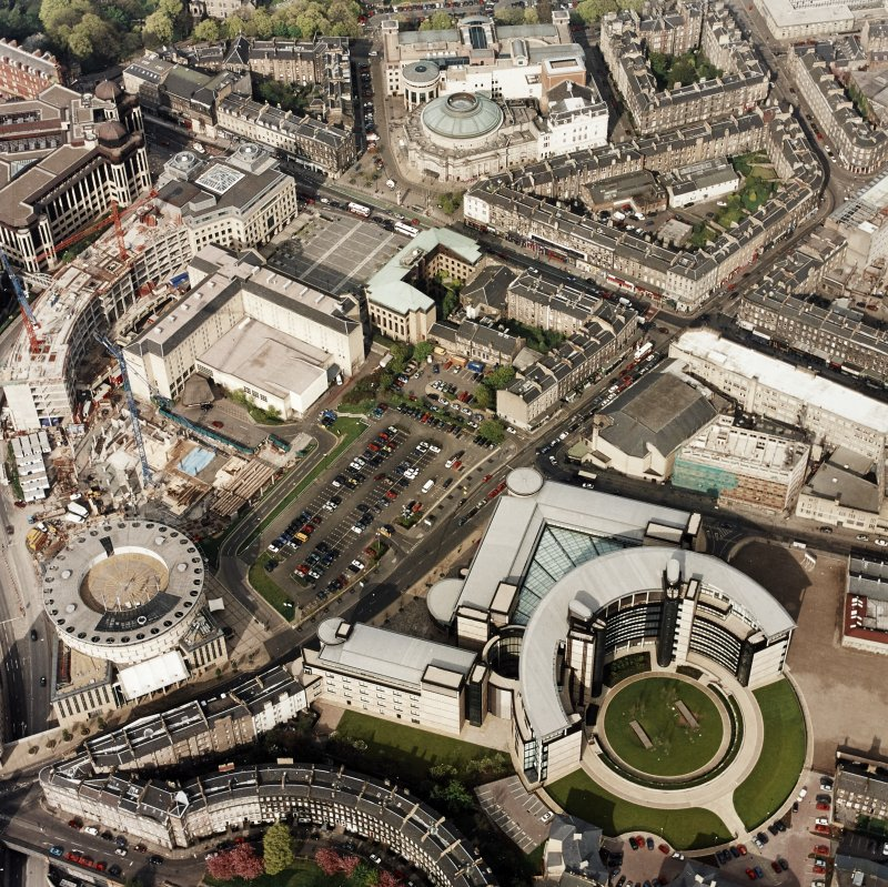 Oblique aerial view of Edinburgh centred on the Scottish Widows building with the construction of Exchange Crescent adjacent, taken from the SW.