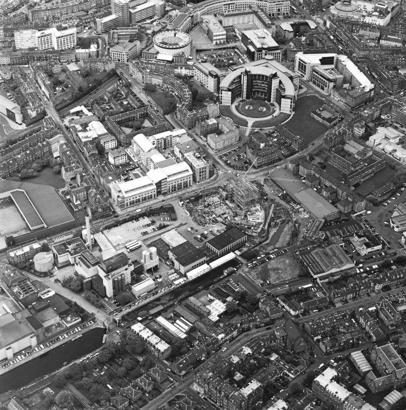 Oblique aerial view centred on the brewery with the canal, canal basin and canal bridge adjacent, taken from the SSW.