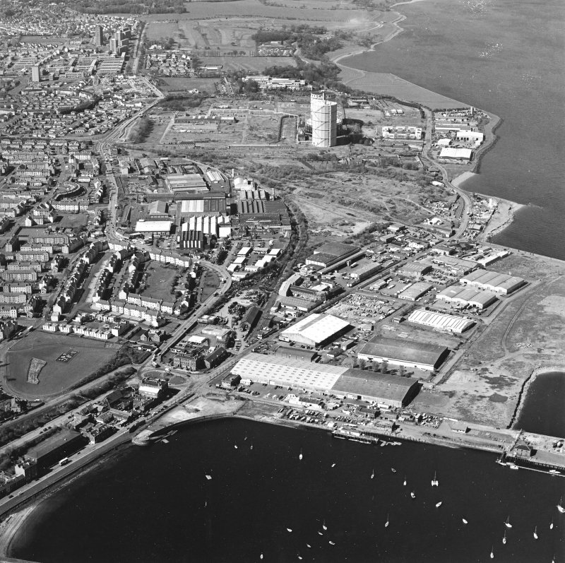 Oblique aerial view centred on the office and works with the harbour, industrial estate and gas works adjacent, taken from the E.