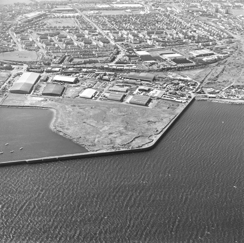 Oblique aerial view centred on the industrial estate with the office, works and harbour adjacent, taken from the N.