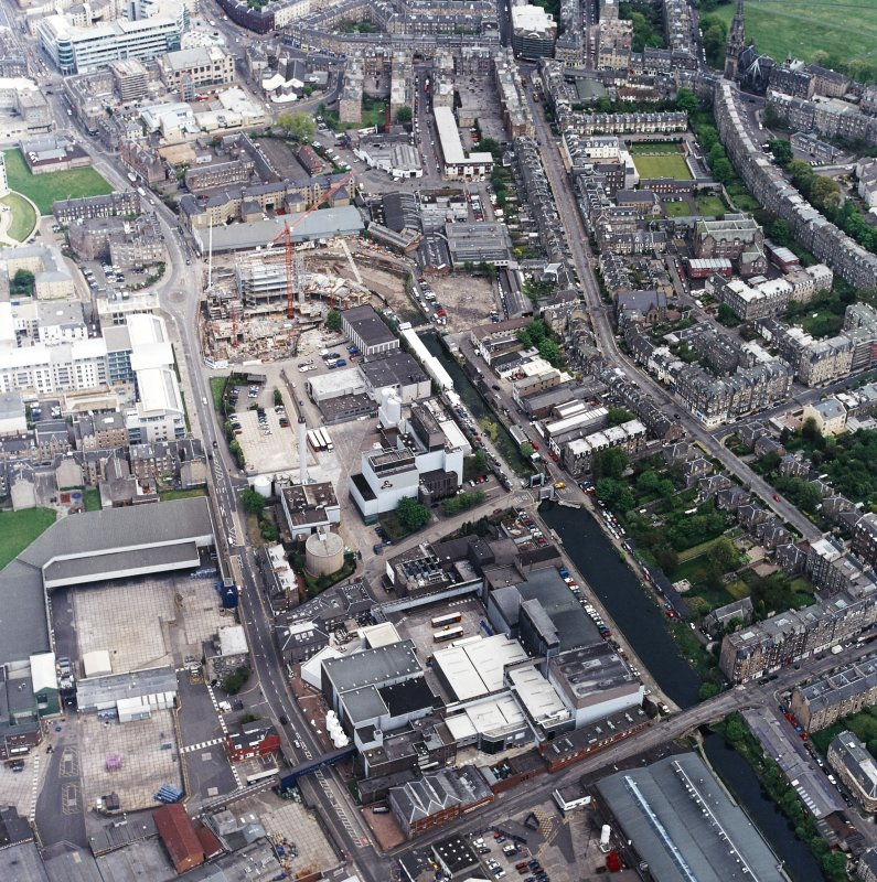 Oblique aerial view centred on the brewery with the leisure centre and cinema, canal, canal basin and canal bridge adjacent, taken from the W.