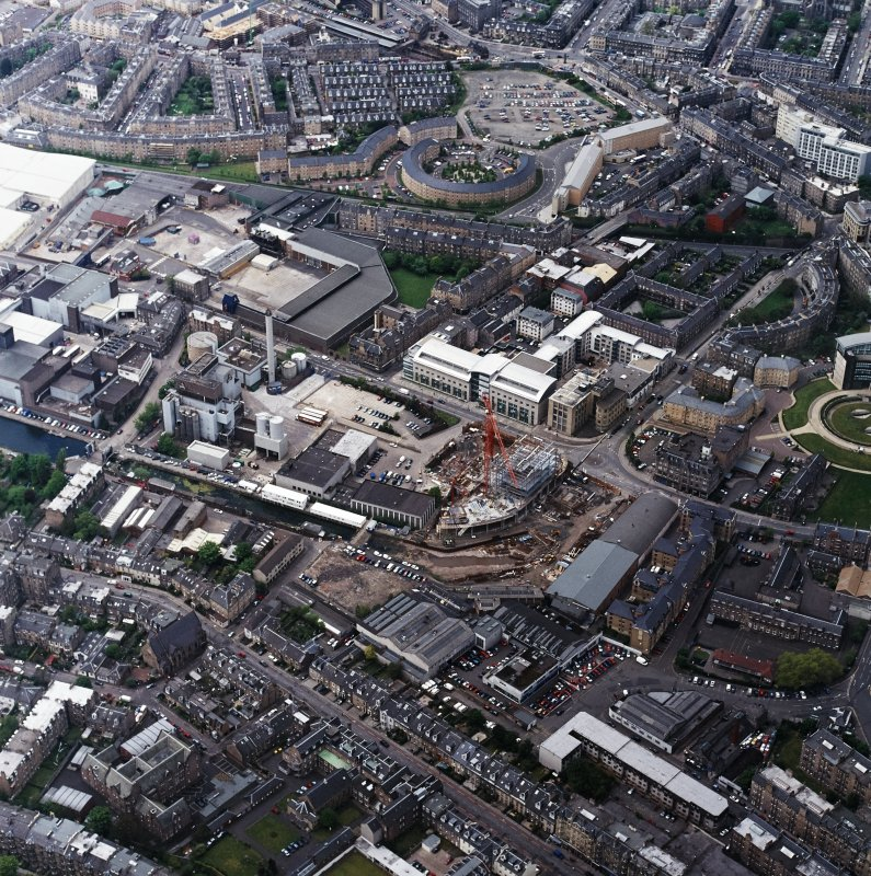 Oblique aerial view centred on the brewery with the canal, canal basin and canal bridge adjacent, taken from the SE.