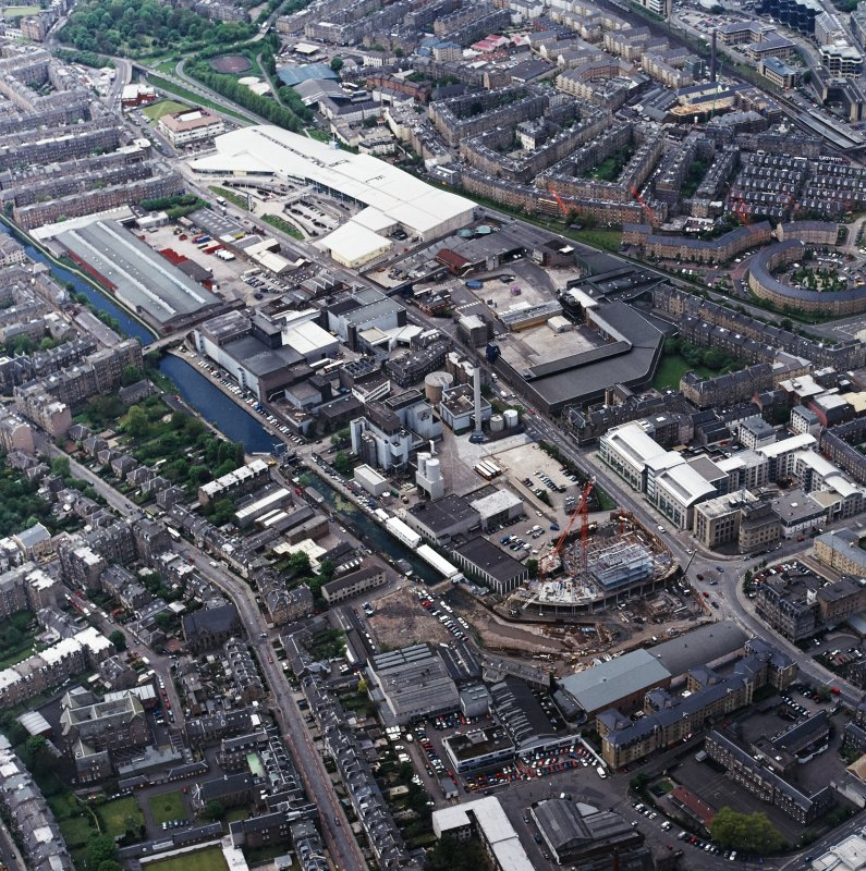 Oblique aerial view centred on the brewery with the leisure centre and cinema, canal, canal basin and canal bridge adjacent, taken from the ESE.