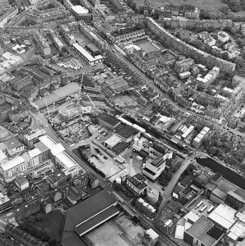 Oblique aerial view centred on the brewery with the canal, canal basin and canal bridge adjacent, taken from the WNW.