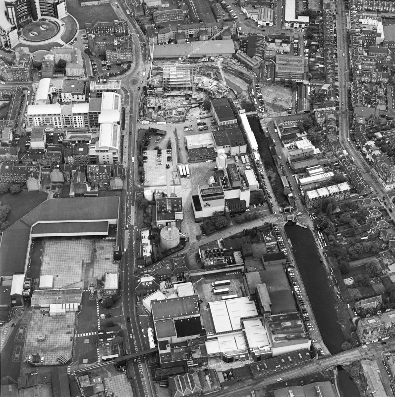 Oblique aerial view centred on the brewery with the canal, canal basin and canal bridge adjacent, taken from the WSW.