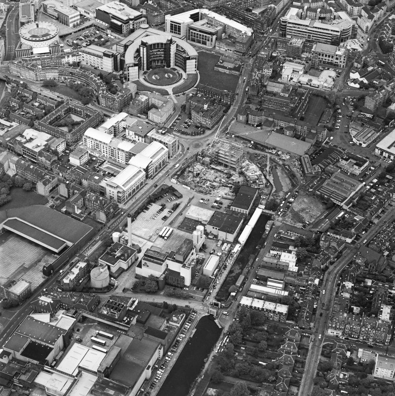 Oblique aerial view centred on the brewery with the canal, canal basin and canal bridge adjacent, taken from the SW.
