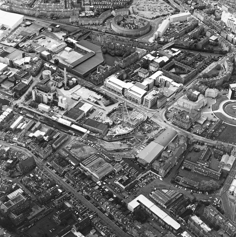 Oblique aerial view centred on the brewery with the leisure centre and cinema, canal, canal basin and canal bridge adjacent, taken from the SE.