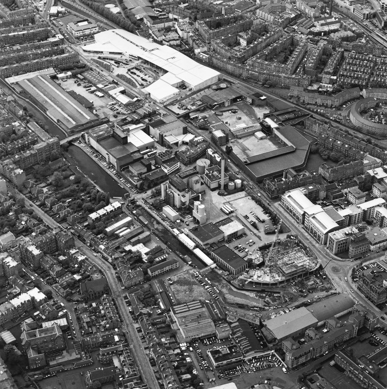 Oblique aerial view centred on the brewery with the leisure centre and cinema, canal, canal basin and canal bridge adjacent, taken from the E.