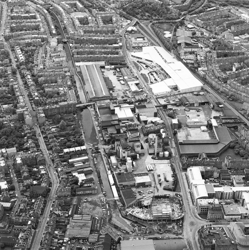 Oblique aerial view centred on the brewery with the leisure centre and cinema, canal, canal basin and canal bridge adjacent, taken from the ENE.