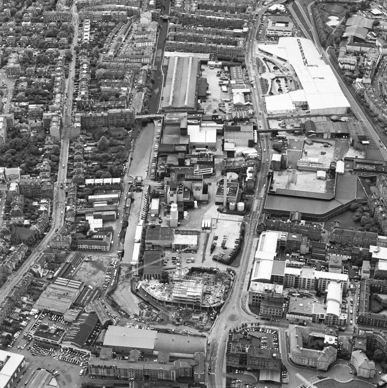 Oblique aerial view centred on the brewery with the leisure centre and cinema, canal, canal basin and canal bridge adjacent, taken from the NE.