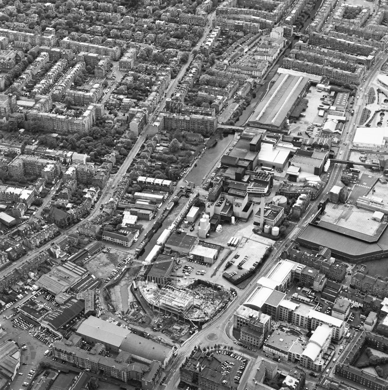 Oblique aerial view centred on the brewery with the canal, canal basin and canal bridge adjacent, taken from the NNE.
