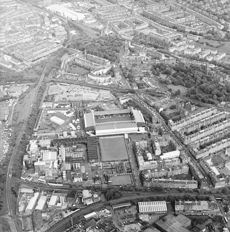 General oblique aerial view centred on the football ground and stadium with the whisky distillery adjacent, taken from the W.