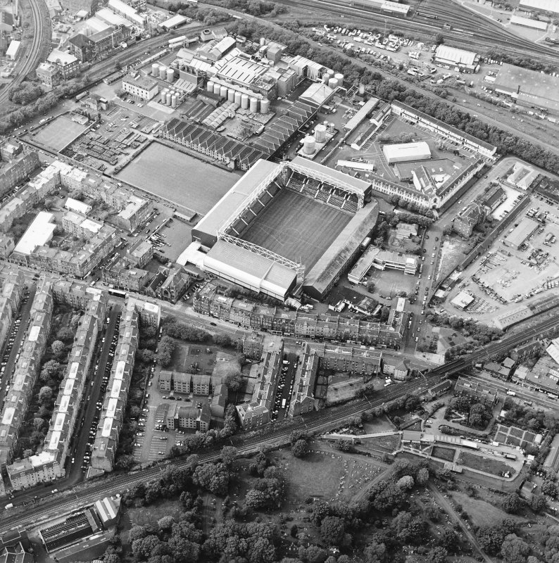 General oblique aerial view centred on the football ground and stadium with the whisky distillery adjacent, taken from the SE.