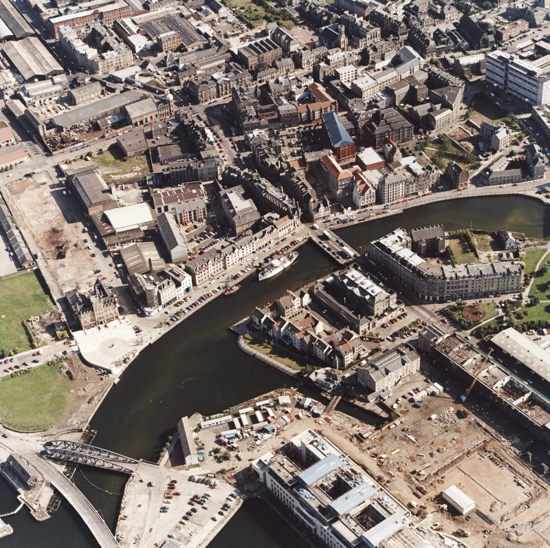 Oblique aerial view, taken from the NW, showing North Leith across the top half of the photograph, and Customs House and the East Old Dock and swing bridge in the bottom half. The Victoria swing bridge is visible in the bottom left-hand corner.