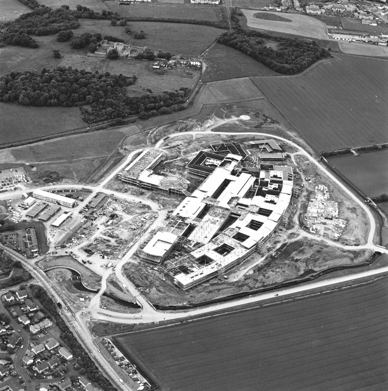 Oblique aerial view centred on the Royal Infirmary of Edinburgh at Little France under construction, taken from the S.
