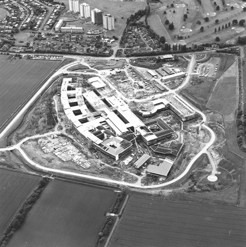 Oblique aerial view centred on the Royal Infirmary of Edinburgh at Little France under construction, taken from the E.