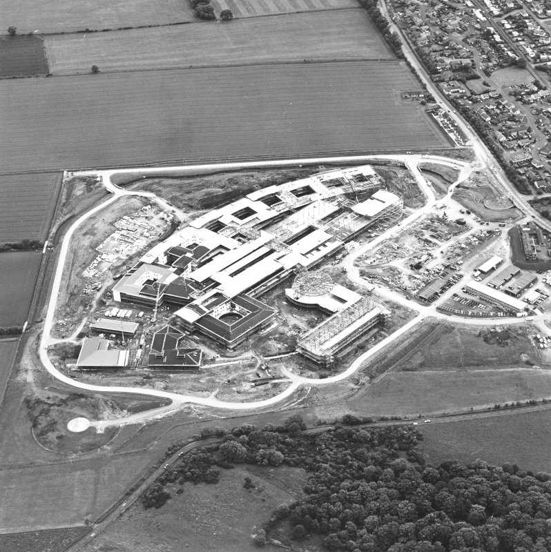 Oblique aerial view centred on the Royal Infirmary of Edinburgh at Little France under construction, taken from the N.