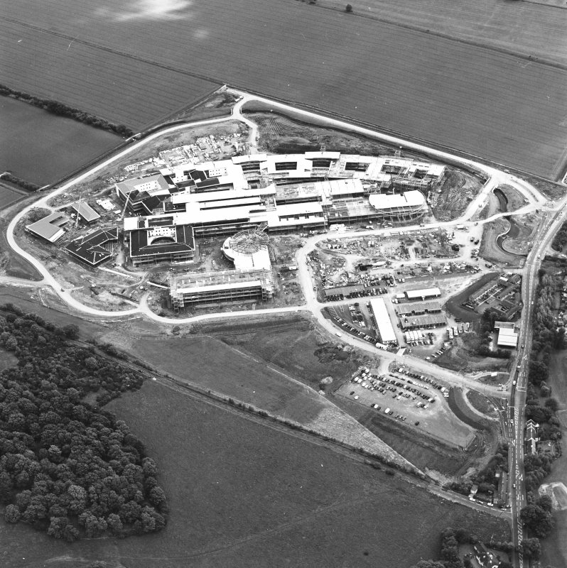 Oblique aerial view centred on the Royal Infirmary of Edinburgh at Little France under construction, taken from the NW.