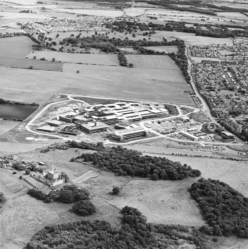 Oblique aerial view centred on the hospital under construction with castle adjacent, taken from the NW.