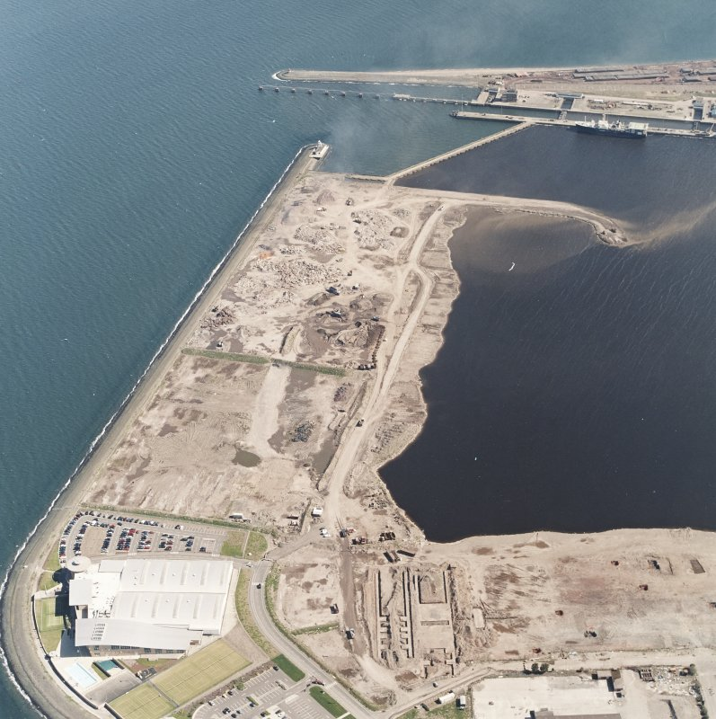 Oblique aerial view centred on the breakwater with the docks adjacent, taken from the SW.