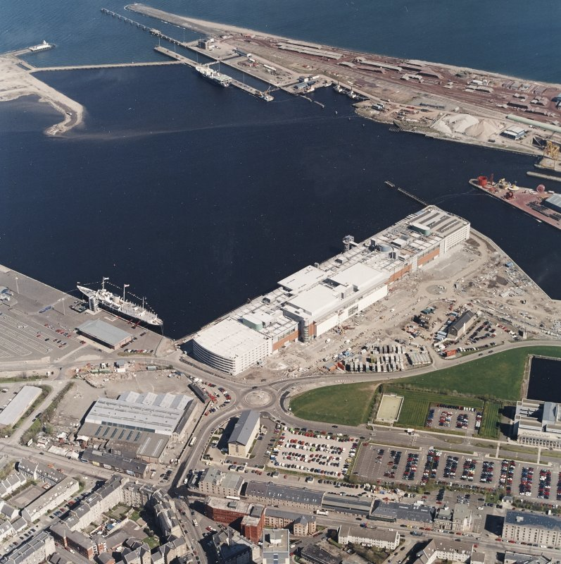 Oblique aerial view centred on the docks and the construction of the shopping centre, cinema, restaurants and visitor centre, taken from the S.