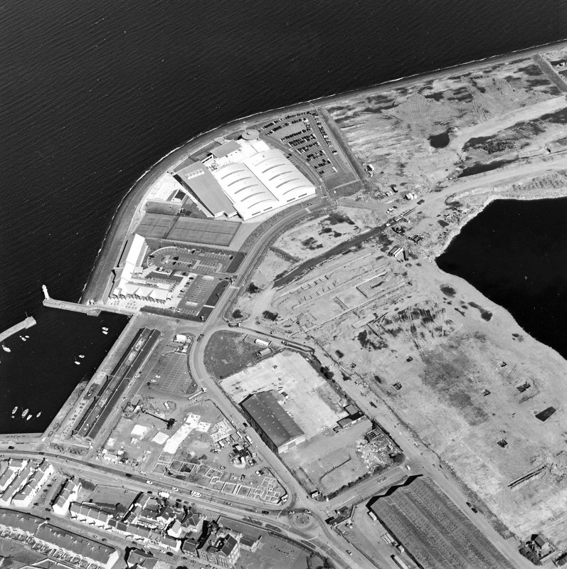 Oblique aerial view centred on the breakwater with the docks, harbour and fishmarket adjacent, taken from the SSE.