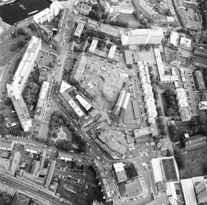 Oblique aerial view centred on the excavation with the warehouses and offices adjacent, taken from the SW.