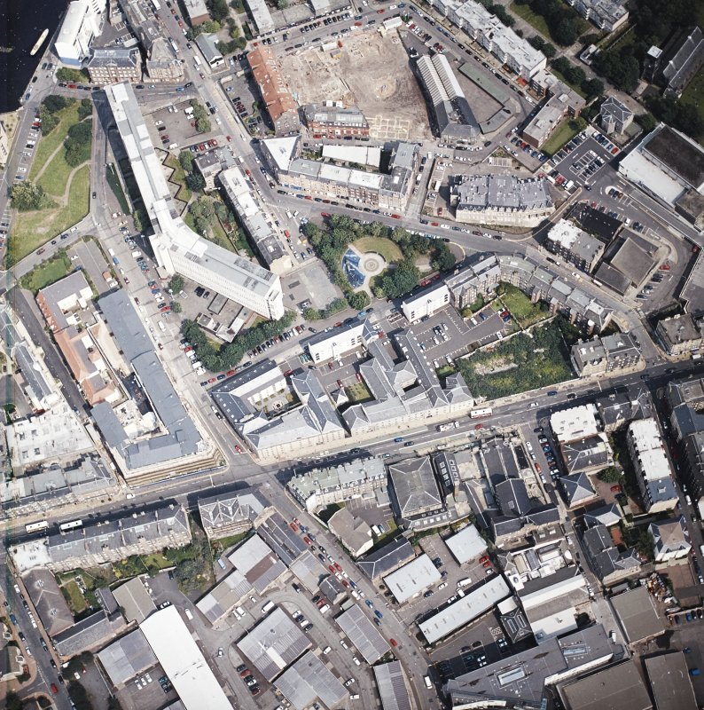 Oblique aerial view of Leith centred on Great Junction Street and Crabbies Winery, taken from the WSW.